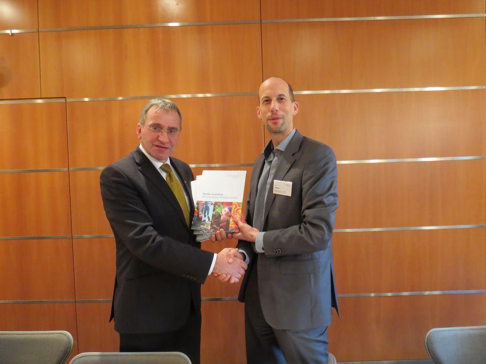 Sven Iversen übergibt Paul Lehrieder, MdB, die Abschlusspublikation